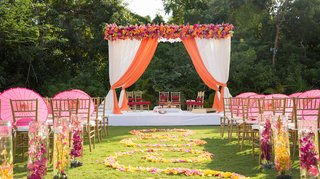 outdoor-indian-wedding-ceremony-with-submerged-yellow-and-magenta-orchids-along-the-aisle