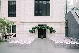 wedding-ceremony-cleveland-museum-of-art-oval-clear-guest-chairs-and-tropical-greenery-chuppah
