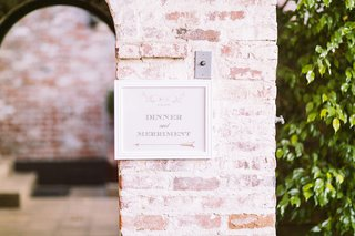 sign-in-white-frame-with-arrow-on-brick-wall-pointing-to-outdoor-wedding-reception