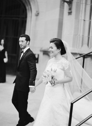 black-and-white-photo-of-bride-and-groom-smiling-as-they-leave-church-wedding-ceremony