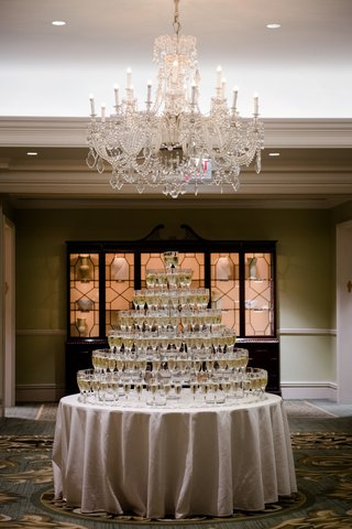 wedding-reception-ballroom-crystal-chandelier-round-table-linen-champagne-tower-champagne-flutes