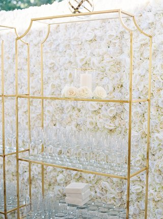 flower-wall-of-ivory-roses-gold-stand-displaying-wine-glasses-at-wedding-reception