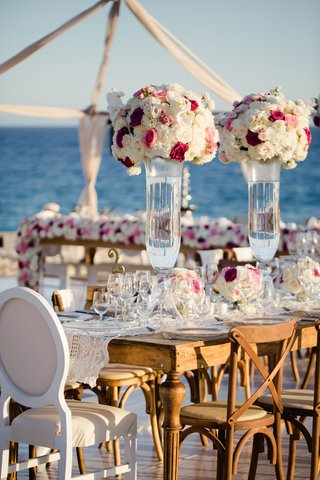 wedding-reception-on-stage-over-sand-at-beach-wood-tables-white-pink-flowers-ocean-view