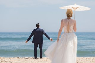 wedding-portrait-groom-with-arms-out-beach-in-montauk-new-york-bride-in-dress-parasol
