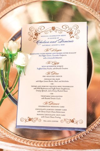formal-wedding-menu-with-gold-and-blue-details-on-reflective-charger-plate