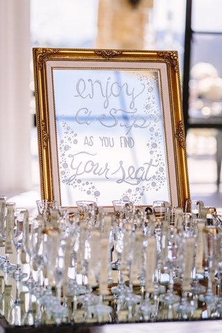 mirrored-sign-for-escort-cards-champagne-flutes-for-guests
