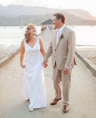 bride-and-groom-holding-hands-on-pier-in-kauai