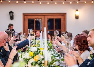 wedding-reception-head-table-white-yellow-flowers-gold-candleholders-wine-glasses-bacara-cheers