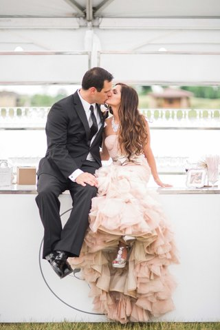 bride-in-blush-vera-wang-mermaid-ruffled-gown-groom-in-black-by-vera-wang-tux-sit-on-bar