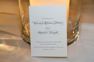 wedding-invitation-with-black-script-against-pillar-candle-hurricane