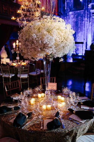 wedding-reception-table-with-a-trumpet-vase-topped-with-babys-breath-and-surrounded-by-candles
