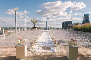 gateway-arch-in-background-white-aisle-runner-lined-with-white-and-pink-flowers-ghost-chairs-sign