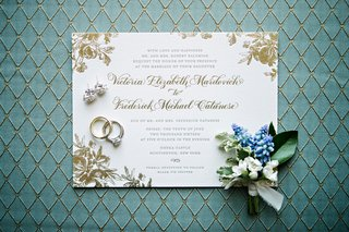 white-wedding-invitation-with-gold-foil-flower-print-and-calligraphy-boutonniere-wedding-rings