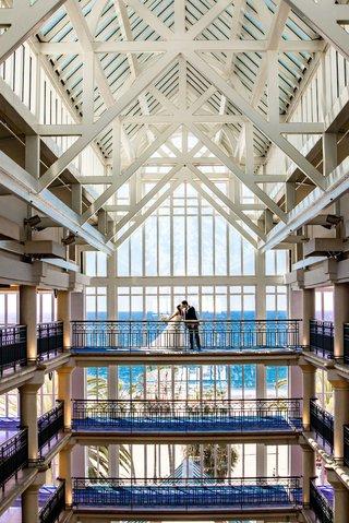 wedding-portrait-bride-and-groom-on-top-floor-of-hotel-atrium-ocean-view-loews-santa-monica