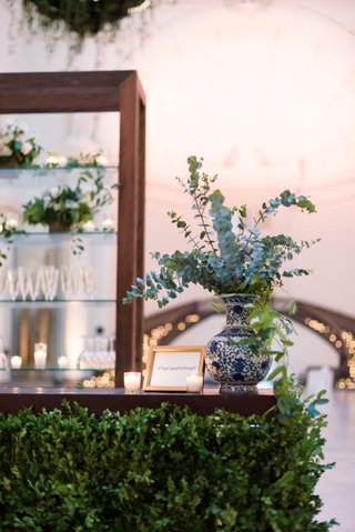 wedding-reception-bar-wood-with-greenery-blue-white-vase-eucalyptus-bar-menu-and-shelving