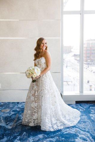 bride-with-hair-worn-down-long-strapless-wedding-dress-flower-applique-sheer-details-white-bouquet