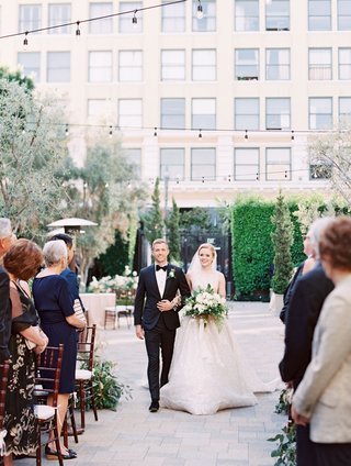 bride-in-high-neck-lazaro-wedding-dress-escort-in-tuxedo-bow-tie-bistro-lights-overhead-vibiana
