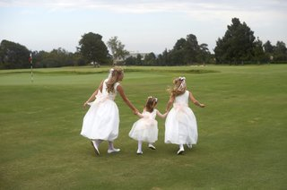 three-girls-in-white-dresses-with-pink-sashes
