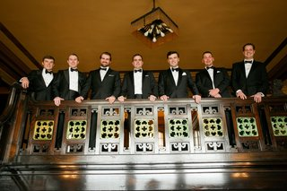 groom-and-groomsmen-black-white-tuxedo-bow-tie-on-balcony-in-church-classic-ensembles