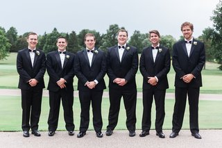 groomsmen-in-front-of-golf-course-with-tuxedos-on-and-bow-ties-from-collared-greens