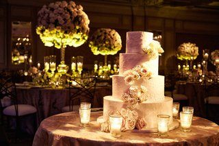 four-layer-wedding-cake-ivory-frosting-fresh-flowers-on-each-layer-candles-on-cake-table