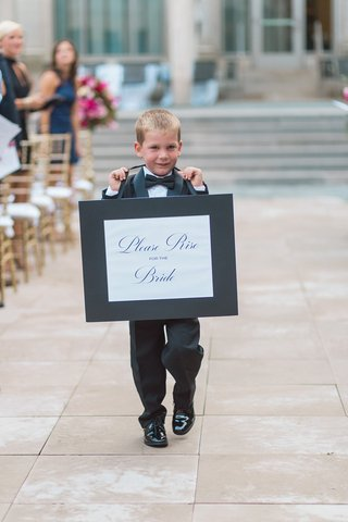 ring-bearer-in-tuxedo-carrying-sign-telling-people-to-rise-for-the-bride