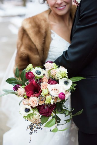 bride-in-fur-stole-and-white-wedding-dress-colorful-bouquet-anemone-greenery-rose-pink-red-blue
