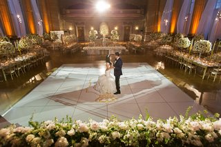 bride-and-groom-on-dance-floor-gold-monogram-no-guests-white-gold-reception-decor-opulent-wedding