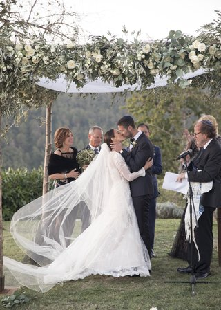 bride-and-groom-kiss-under-chuppah-with-natural-posts-ivory-flowers-and-greenery