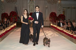 bridesmaid-in-black-groomsman-in-tuxedo-walking-pugs-down-aisle