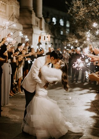 bride-in-wedding-dress-with-fur-wrap-long-hair-headpiece-guests-with-sparklers-groom-in-white-jacket