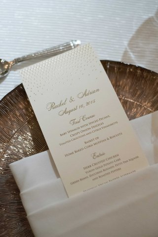 a-champagne-colored-reception-menu-with-gold-calligraphy-on-white-tablescape