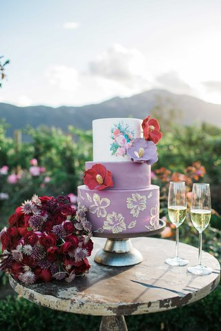 purple-red-pink-wedding-cake-sugar-floral-detailing-with-gold-on-rustic-table-on-vineyard-dessert
