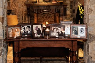 wood-table-at-wedding-reception-with-portraits-of-the-bride-and-grooms-families