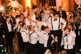 bride-and-groom-in-chairs-during-wedding-reception-hora-dance-jewish-wedding-tradition