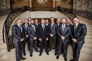 groom-in-black-suit-groomsmen-in-blue-grey-suits-with-sheen
