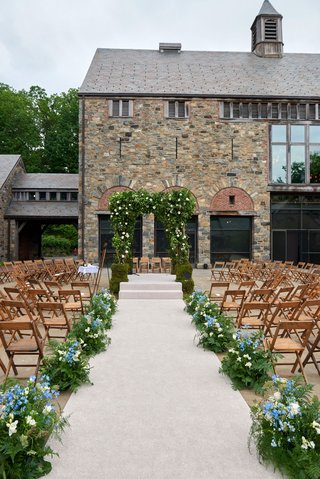 wedding-guests-seated-in-the-round-new-york-farm-venue-blue-flowers-greenery-wood-chairs-stone-venue