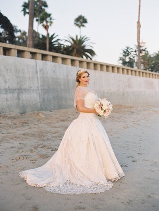 bride-in-wedding-dress-eve-of-milady-lace-short-sleeves-sheer-details-bouquet-on-beach