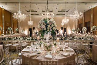 wedding-reception-hotel-ballroom-round-table-tall-centerpiece-clear-chairs-head-table-chandeliers