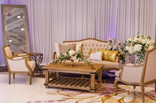 wedding-reception-wood-coffee-table-tufted-settee-armchair-flowers-gold-pillows-drapery-custom-floor