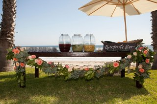 wood-rustic-table-with-flower-greenery-garland-margarita-bar-wood-sign-umbrella-margaritas-in-drink