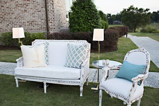 outdoor-lounge-area-with-vintage-white-seating-and-blue-and-white-throw-pillows