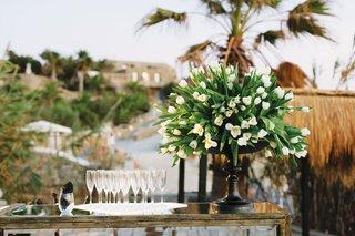 wedding-reception-bar-tulip-flower-arrangement-black-vessel-champagne-flutes-on-tray-mirror-bar