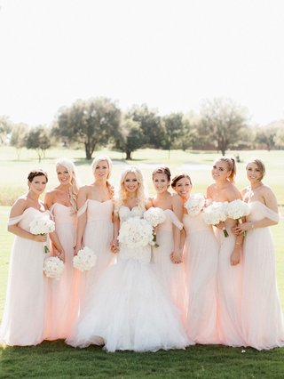 bride-in-trumpet-gown-with-large-white-bouquet-and-bridesmaids-in-light-pink-off-shoulder-long-dress