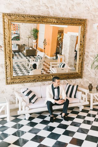 wedding-portrait-groom-in-colombia-on-white-sofa-black-white-checker-floor-gold-mirror-lobby-hotel