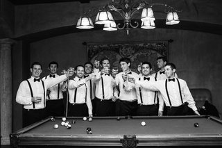 black-and-white-photo-of-groom-and-groomsmen-at-pool-table