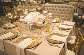 wedding-reception-table-with-gold-chargers-flatware-stemware-tan-napkins-tablecloth