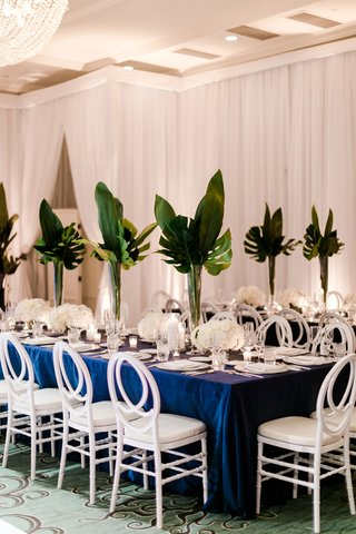 wedding-reception-long-table-navy-blue-linen-white-chair-white-flowers-tall-greenery-tropical-palms