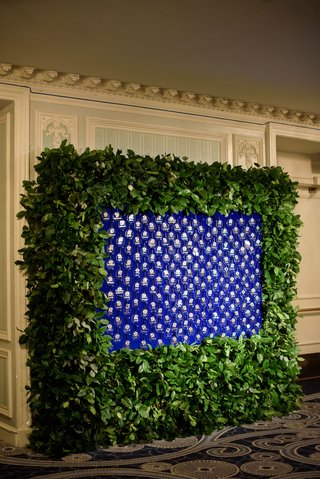 escort-card-display-glass-ornaments-on-blue-background-framed-with-green-leaves-greenery-hedge-wall