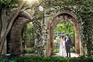 groom-in-tuxedo-bride-in-galia-lahav-wedding-dress-lace-removable-long-sleeves-church-courtyard-chi